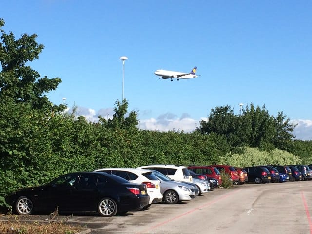 airplane flying over an airport parking lot with cars parked