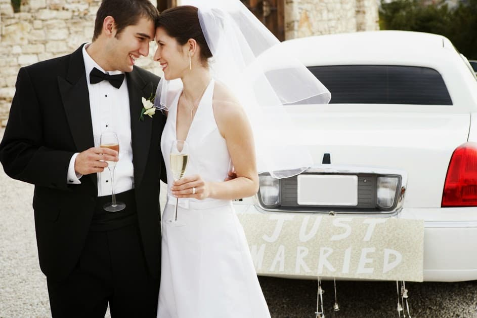 Newly married couple getting ready to ride off in a limo